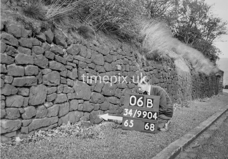 SD990406B, Man marking Ordnance Survey minor control revision point with an arrow in 1950s