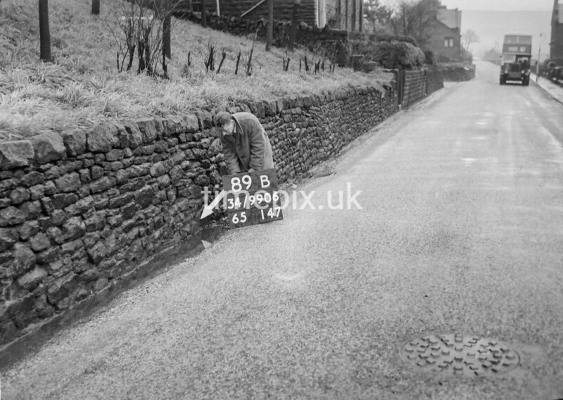 SD990689B2, Man marking Ordnance Survey minor control revision point with an arrow in 1950s