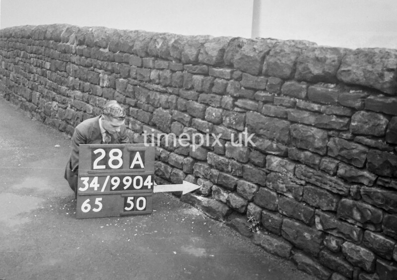 SD990428A, Man marking Ordnance Survey minor control revision point with an arrow in 1950s
