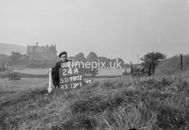 SD980224A, Man marking Ordnance Survey minor control revision point with an arrow in 1950s