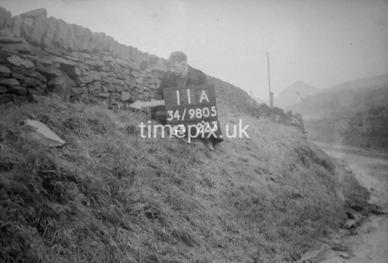 SD980511A, Man marking Ordnance Survey minor control revision point with an arrow in 1950s