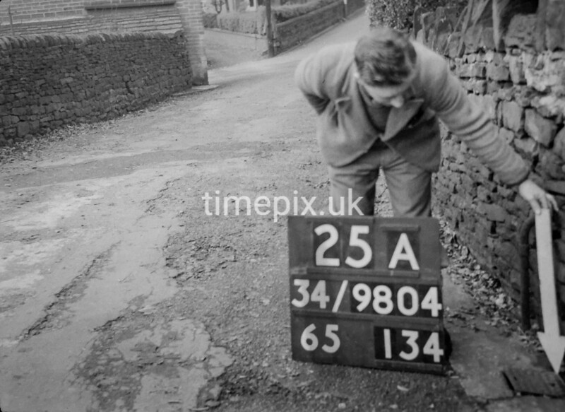 SD980425A, Man marking Ordnance Survey minor control revision point with an arrow in 1950s