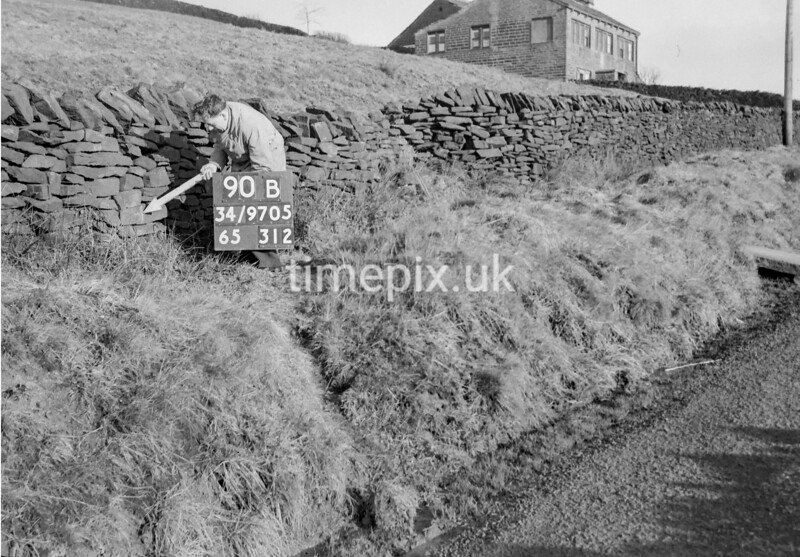 SD970590B, Man marking Ordnance Survey minor control revision point with an arrow in 1950s