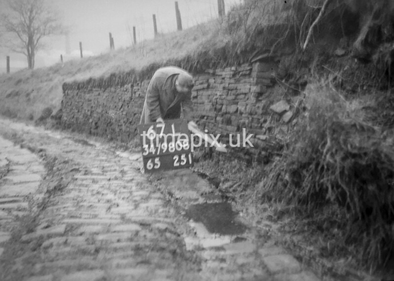 SD980867L, Man marking Ordnance Survey minor control revision point with an arrow in 1950s