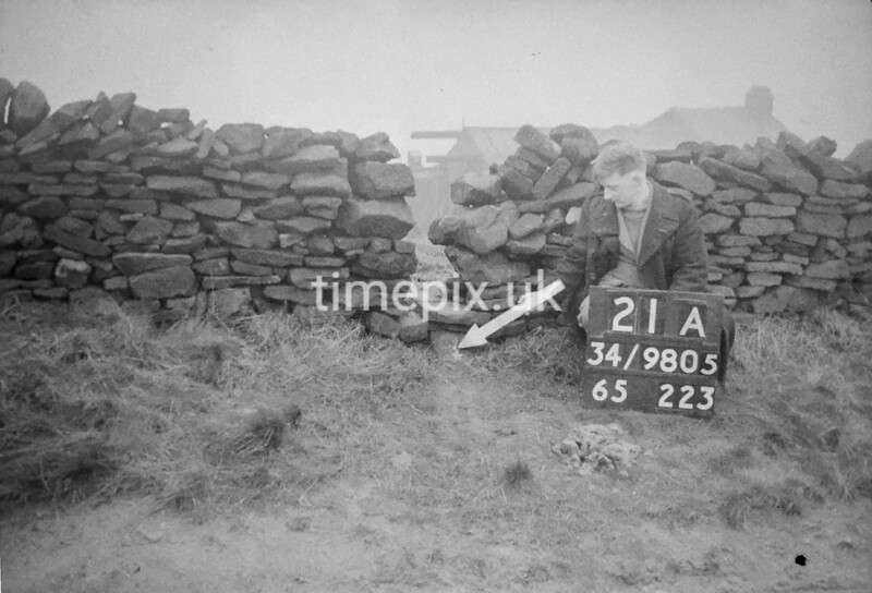 SD980521A, Man marking Ordnance Survey minor control revision point with an arrow in 1950s