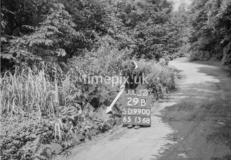 SD990029B, Man marking Ordnance Survey minor control revision point with an arrow in 1950s