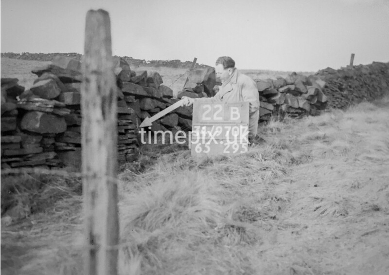 SD970722B, Man marking Ordnance Survey minor control revision point with an arrow in 1950s