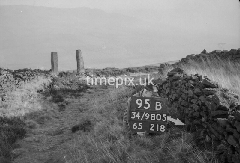SD980595B, Man marking Ordnance Survey minor control revision point with an arrow in 1950s