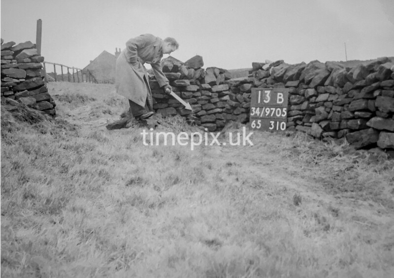 SD970513B, Man marking Ordnance Survey minor control revision point with an arrow in 1950s