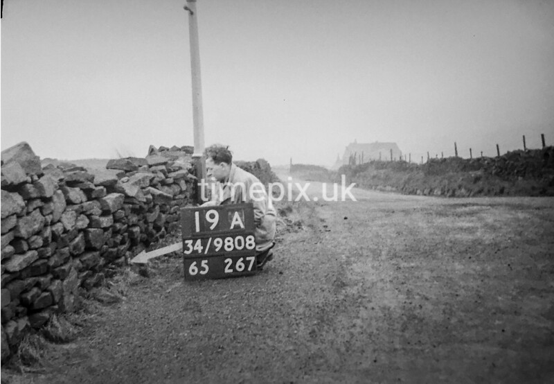 SD980819A, Man marking Ordnance Survey minor control revision point with an arrow in 1950s
