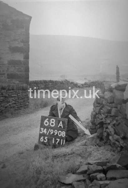 SD990868A, Man marking Ordnance Survey minor control revision point with an arrow in 1950s