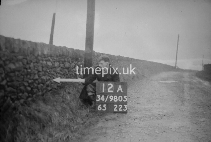 SD980512A, Man marking Ordnance Survey minor control revision point with an arrow in 1950s