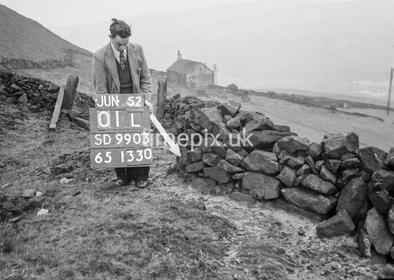 SD990301L, Man marking Ordnance Survey minor control revision point with an arrow in 1950s