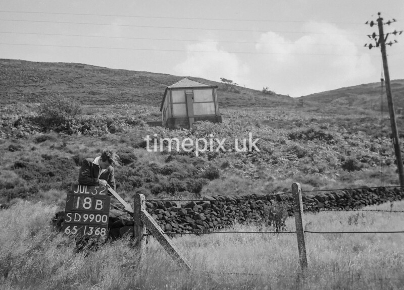 SD990018B, Man marking Ordnance Survey minor control revision point with an arrow in 1950s