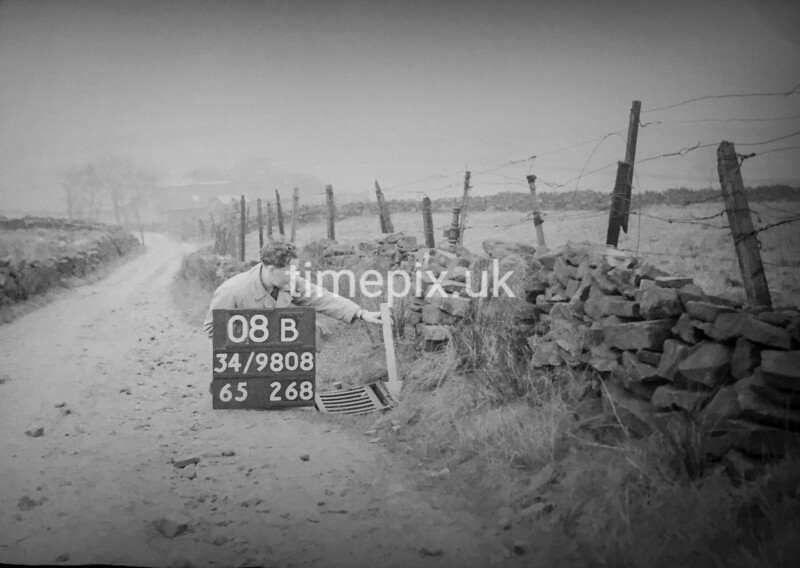 SD980808B, Man marking Ordnance Survey minor control revision point with an arrow in 1950s