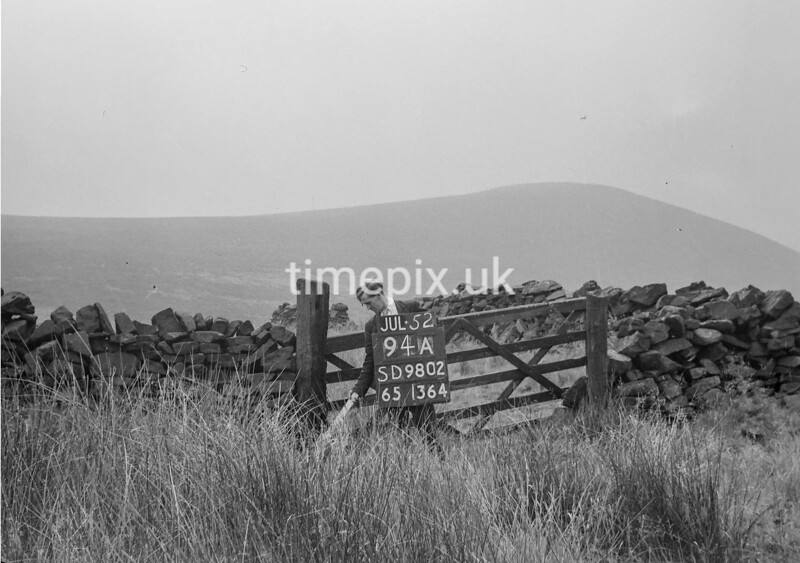 SD980294A, Man marking Ordnance Survey minor control revision point with an arrow in 1950s