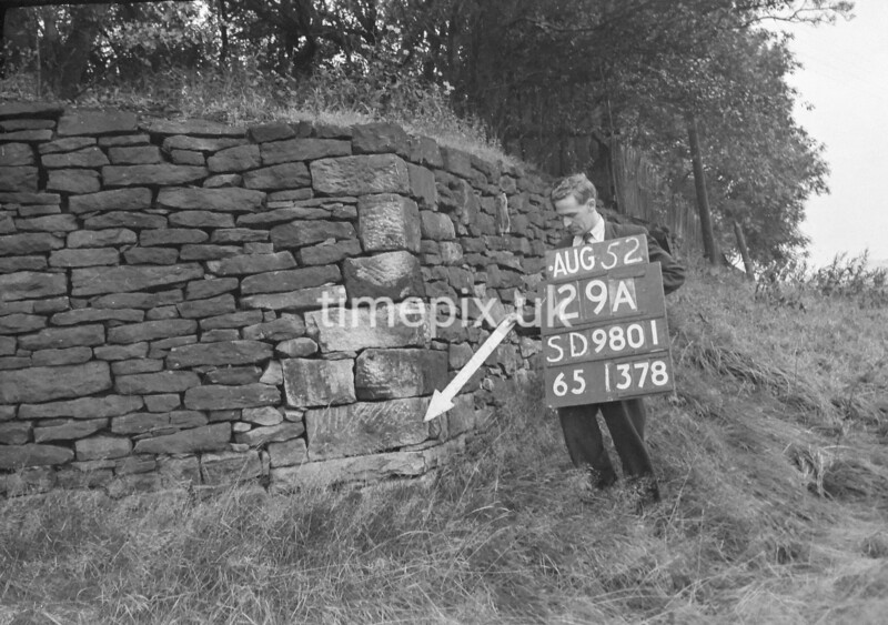 SD980129A, Man marking Ordnance Survey minor control revision point with an arrow in 1950s