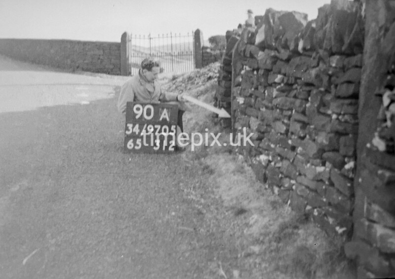 SD970590A, Man marking Ordnance Survey minor control revision point with an arrow in 1950s