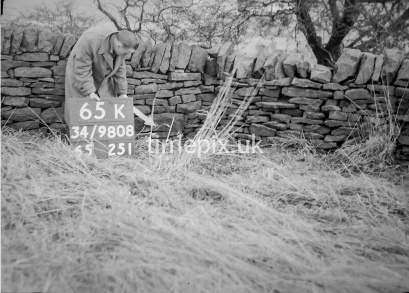 SD980865K, Man marking Ordnance Survey minor control revision point with an arrow in 1950s