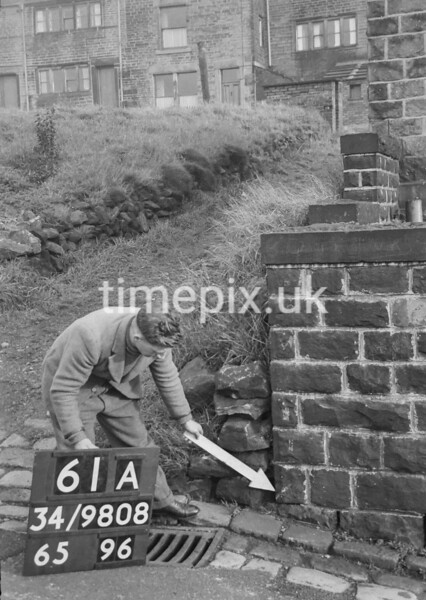 SD980861A, Man marking Ordnance Survey minor control revision point with an arrow in 1950s