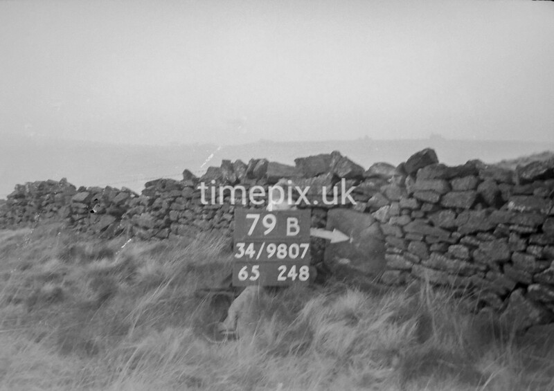 SD980779B, Man marking Ordnance Survey minor control revision point with an arrow in 1950s