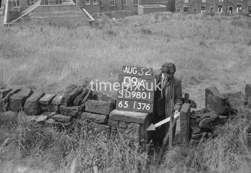 SD980109A, Man marking Ordnance Survey minor control revision point with an arrow in 1950s