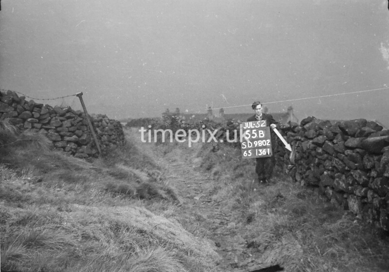 SD980255B, Man marking Ordnance Survey minor control revision point with an arrow in 1950s