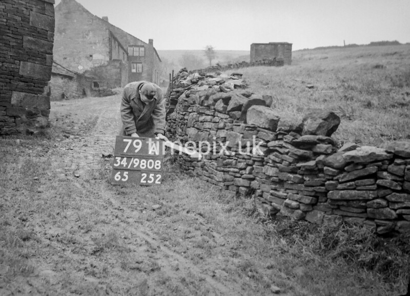 SD980879A, Man marking Ordnance Survey minor control revision point with an arrow in 1950s