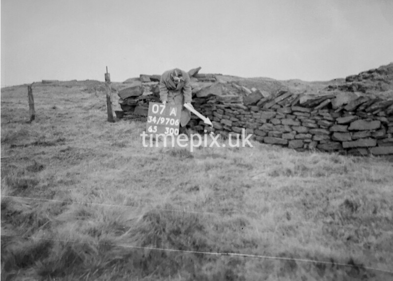 SD970607A, Man marking Ordnance Survey minor control revision point with an arrow in 1950s