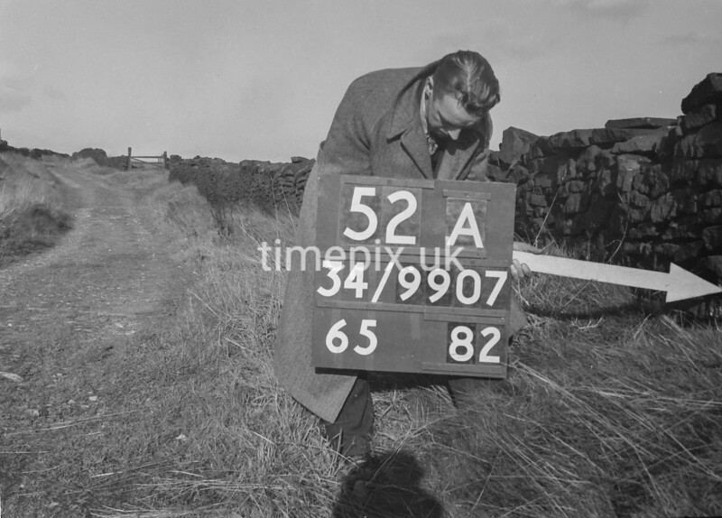 SD990752A, Man marking Ordnance Survey minor control revision point with an arrow in 1950s