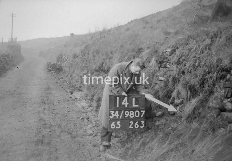 SD980714L, Man marking Ordnance Survey minor control revision point with an arrow in 1950s