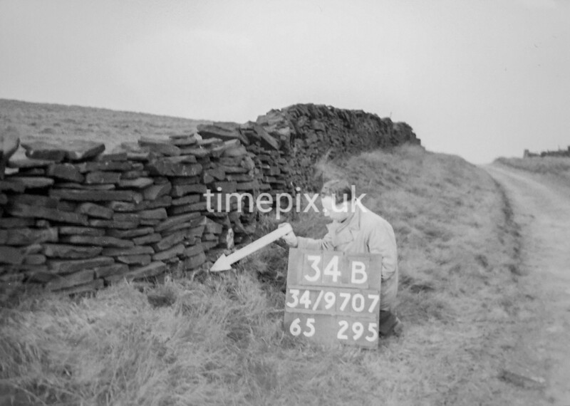 SD970734B, Man marking Ordnance Survey minor control revision point with an arrow in 1950s