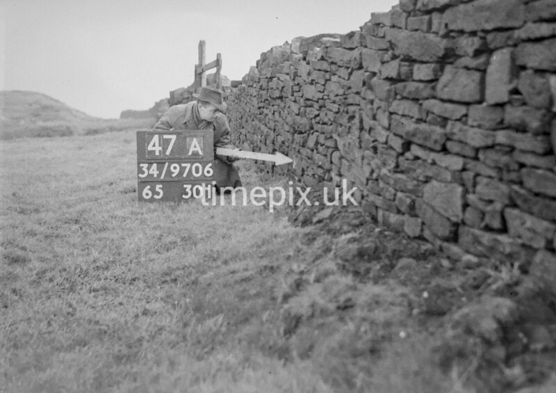 SD970647A, Man marking Ordnance Survey minor control revision point with an arrow in 1950s