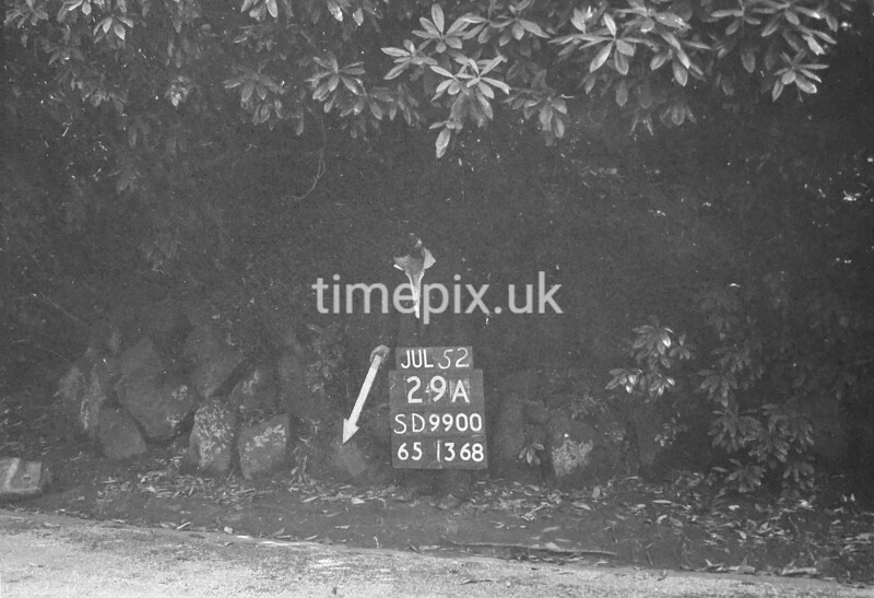 SD990029A, Man marking Ordnance Survey minor control revision point with an arrow in 1950s