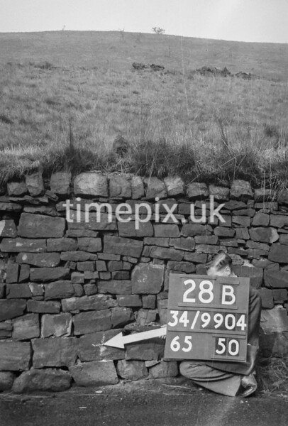 SD990428B, Man marking Ordnance Survey minor control revision point with an arrow in 1950s