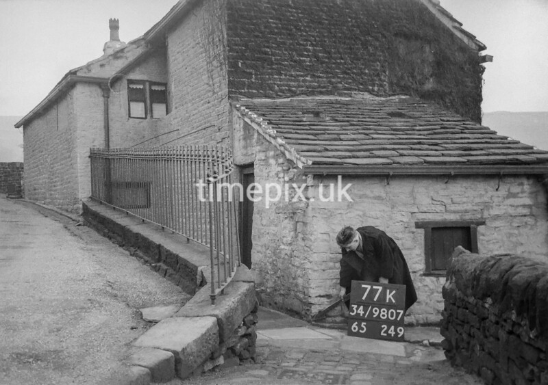 SD980777K, Man marking Ordnance Survey minor control revision point with an arrow in 1950s