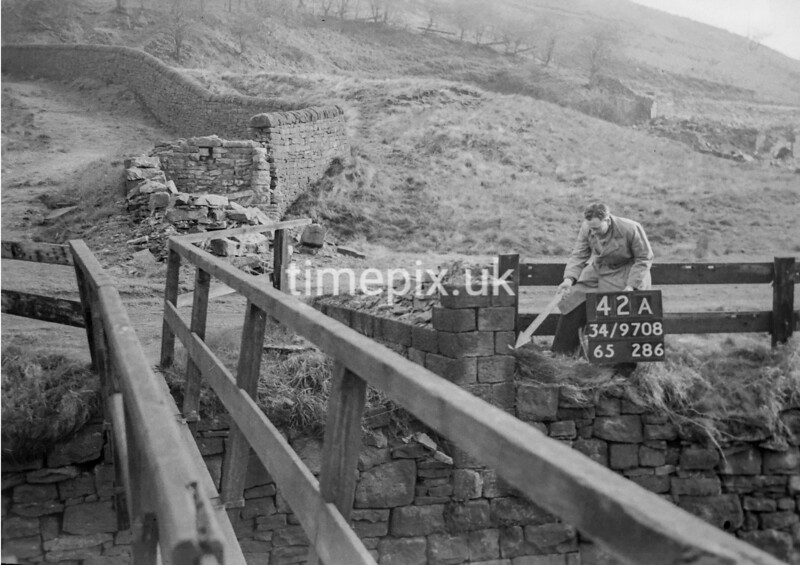 SD970842B, Man marking Ordnance Survey minor control revision point with an arrow in 1950s