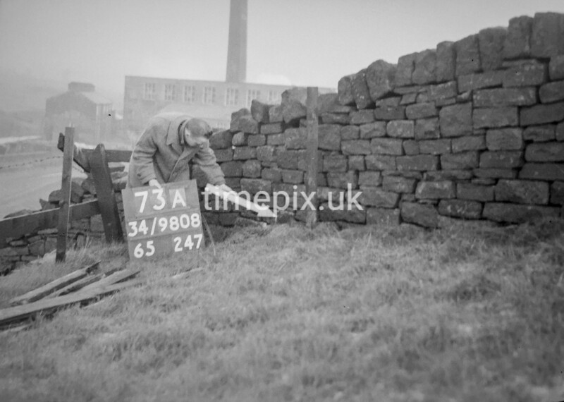 SD980873A, Man marking Ordnance Survey minor control revision point with an arrow in 1950s