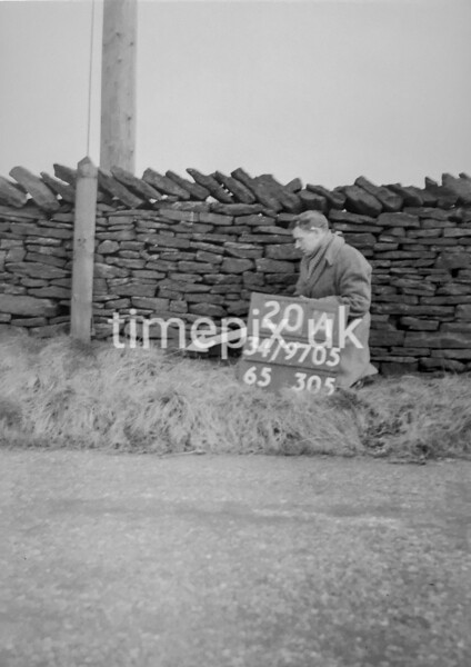 SD970520A, Man marking Ordnance Survey minor control revision point with an arrow in 1950s
