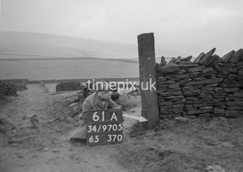SD970561A, Man marking Ordnance Survey minor control revision point with an arrow in 1950s