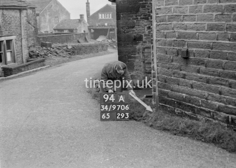 SD970694A, Man marking Ordnance Survey minor control revision point with an arrow in 1950s