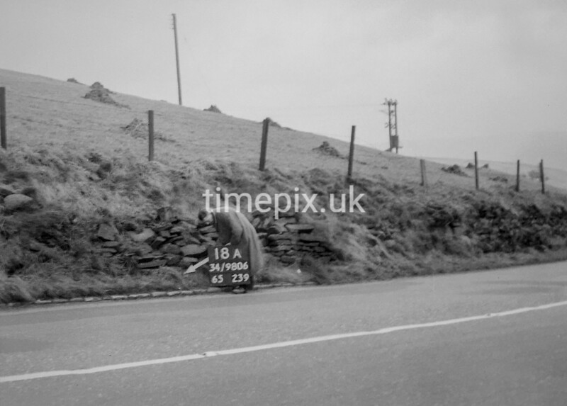 SD980618A, Man marking Ordnance Survey minor control revision point with an arrow in 1950s