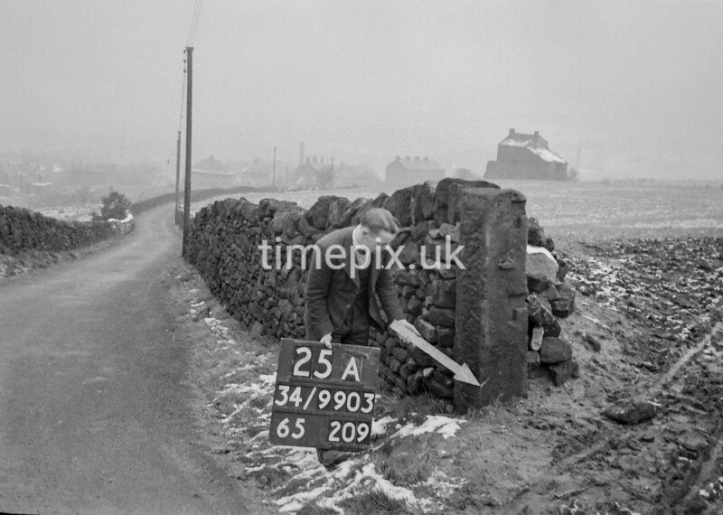 SD990325A, Man marking Ordnance Survey minor control revision point with an arrow in 1950s