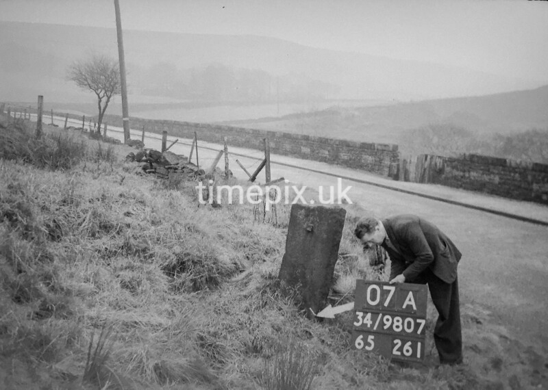 SD980707A, Man marking Ordnance Survey minor control revision point with an arrow in 1950s