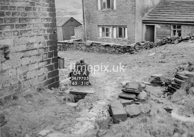 SD970504A, Man marking Ordnance Survey minor control revision point with an arrow in 1950s