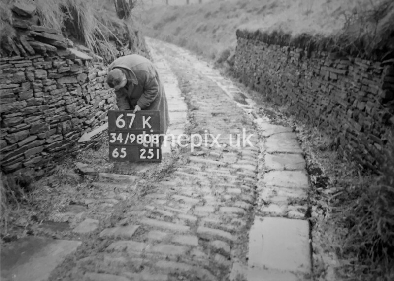 SD980867K, Man marking Ordnance Survey minor control revision point with an arrow in 1950s