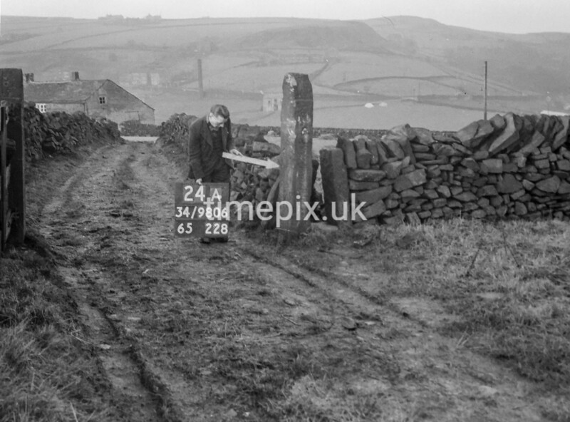 SD980624A, Man marking Ordnance Survey minor control revision point with an arrow in 1950s