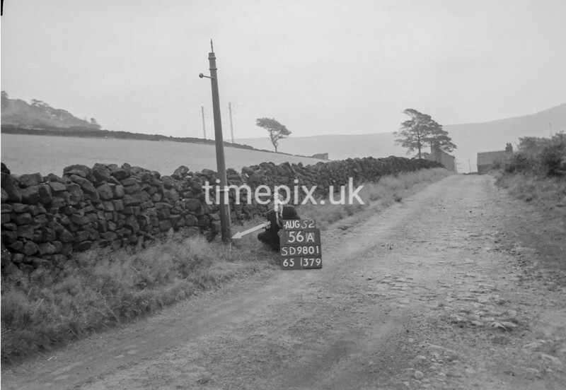 SD980156A, Man marking Ordnance Survey minor control revision point with an arrow in 1950s