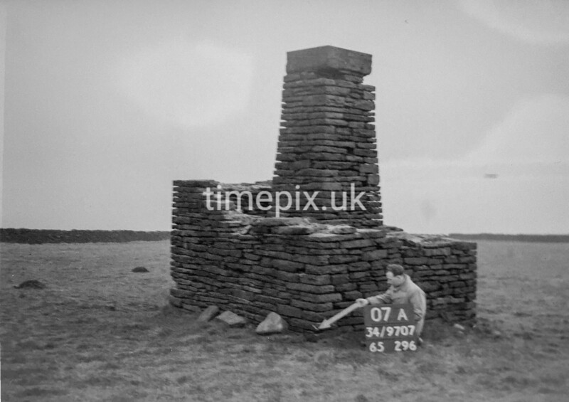 SD970707A, Man marking Ordnance Survey minor control revision point with an arrow in 1950s