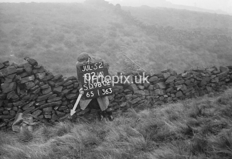SD980202A, Man marking Ordnance Survey minor control revision point with an arrow in 1950s